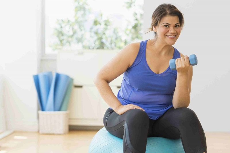 smiling woman sitting on sofa with a light dumbbell in hand