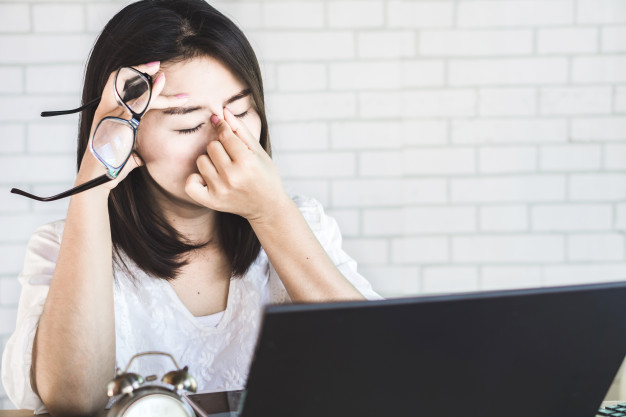 Asian woman working with her laptop and getting tired of wearing eyeglasses