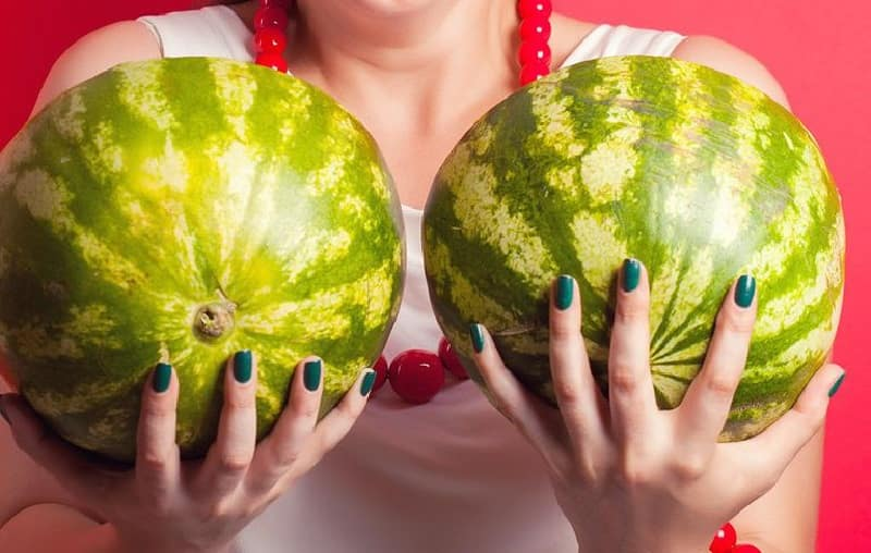 woman holding two watermelons in front of her chest, signifying too large breasts