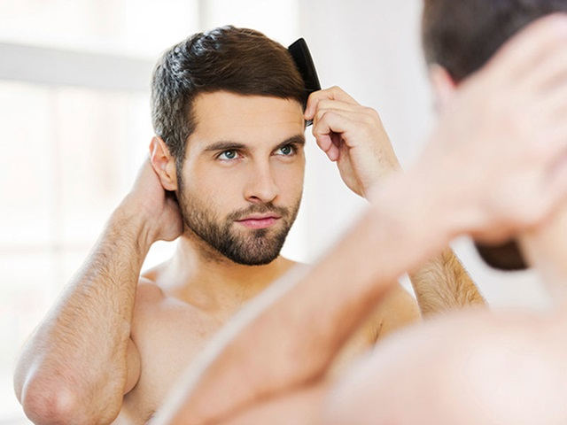 man brushing his hair in front of a mirror after getting hair transplant