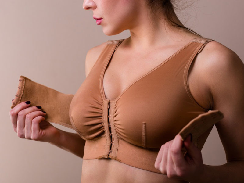 woman with post-surgical bra after breast augmentation