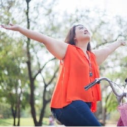 happy woman riding bicycle after weight loss surgery