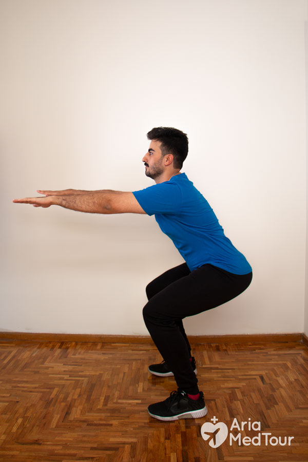 man doing half squat as a knee pain exercise at home