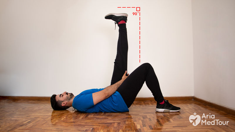 young man doing knee exercises at home, lying down hamstring stretch