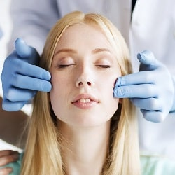 woman getting face examined by plastic surgeon