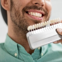 a set of dental veneers held in front of a smiling man's face