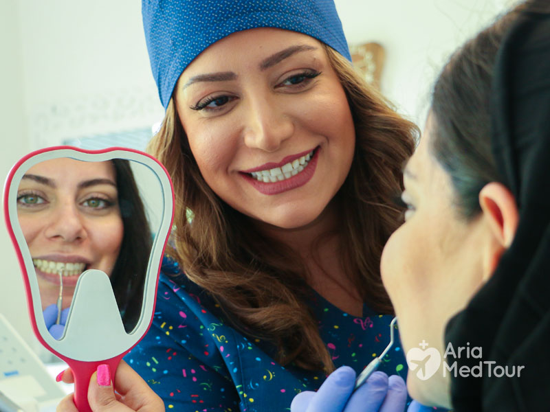 female dentists checking teeth of a woman while she is looking in the mirror
