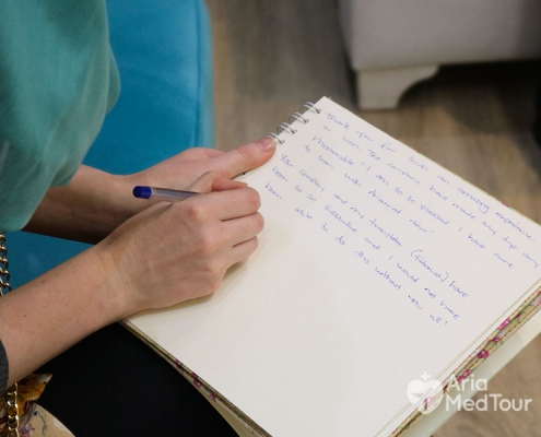 hands of a medical tourist who is writing an English note to thank the staff of the company