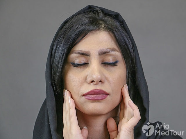 woman wearing black scarf checking out her face to see any sign of aging