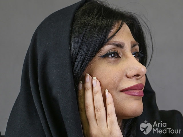 woman wearing black scarf checking out her face to see improvement after facelift