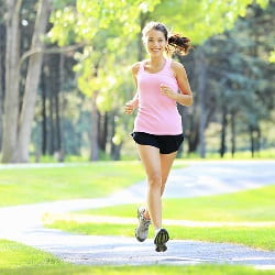 young woman wearing shorts and sleeveless top jogging in a park