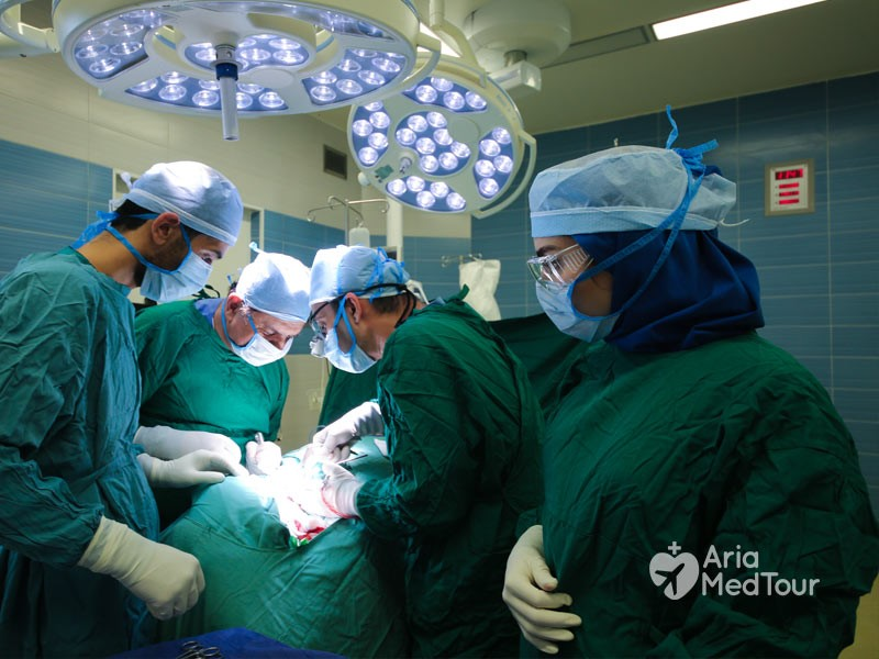 four Iranian surgeons in green uniforms operating on a patient