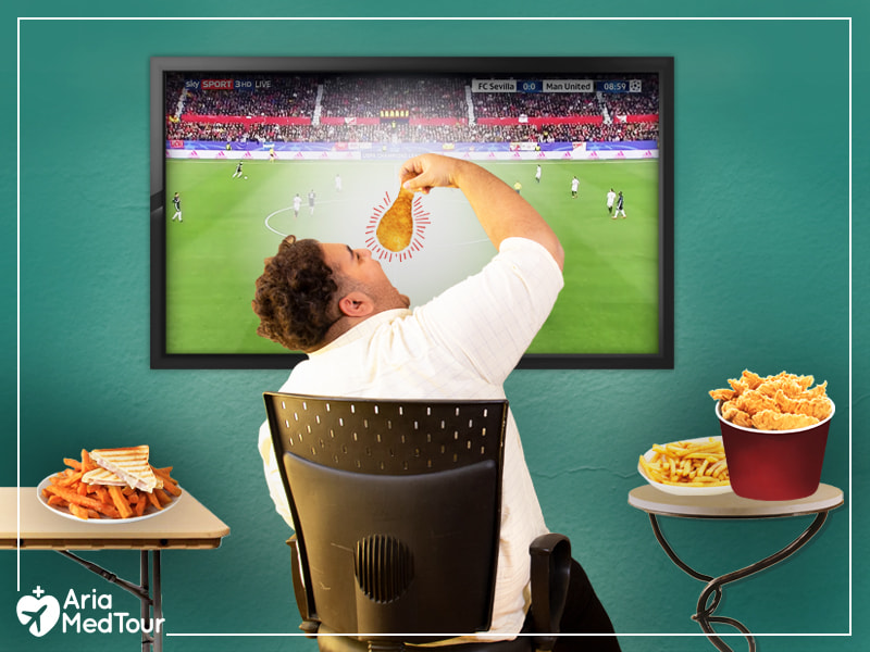 obese man eating lots of processed foods sitting on a chair in front of TV which shows football match