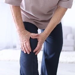 elderly man holding his knee indicating he suffers from arthritis pain