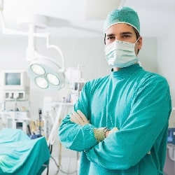 surgeon wearing mask and green uniform posing for a photo with crossed arms with surgical equipment in background