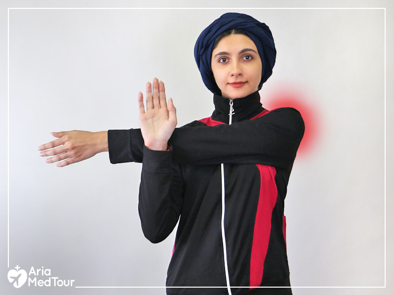 Muslim girl doing shoulder stretch to relieve her shoulder pain