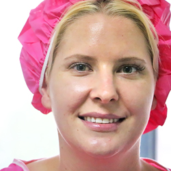 happy woman wearing patient gown and head cap to get ready for rhinoplasty surgery