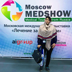 AriaMedTour representative posing for a photo in front of Moscow MedShow Exhibition banner
