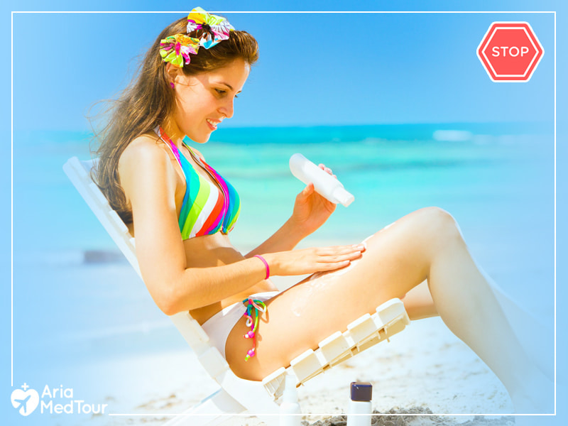 woman sitting in a beach and applying cream on her skin while it should be avoided after breast aug