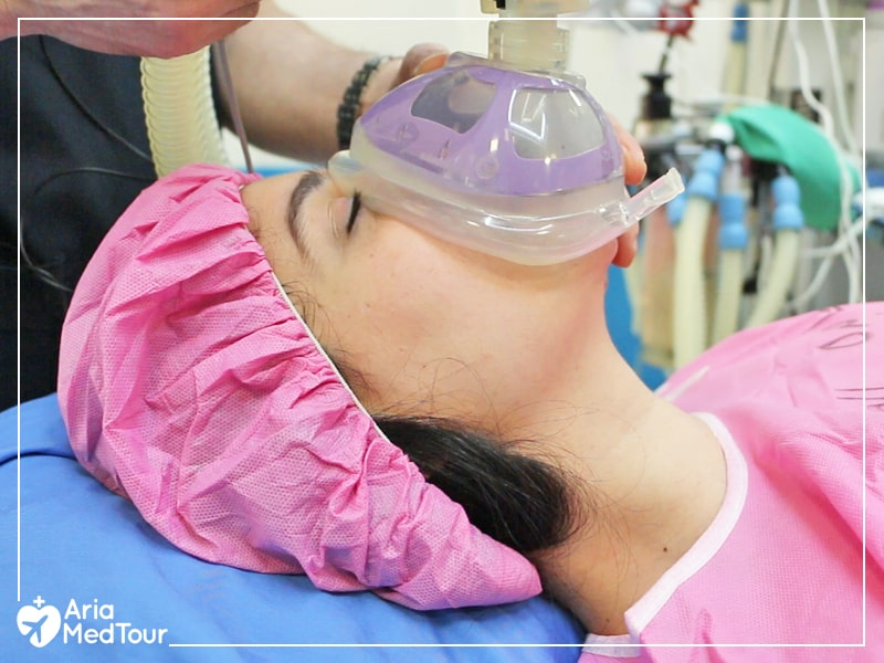 patient wearing pink clothes getting general anesthetics via a mask before suregry