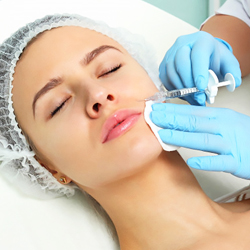 doctor wearing blue gloves injecting dermal fillers into the laugh line of a woman