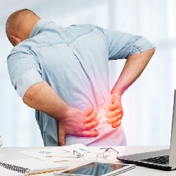 man with low back pain holding his back