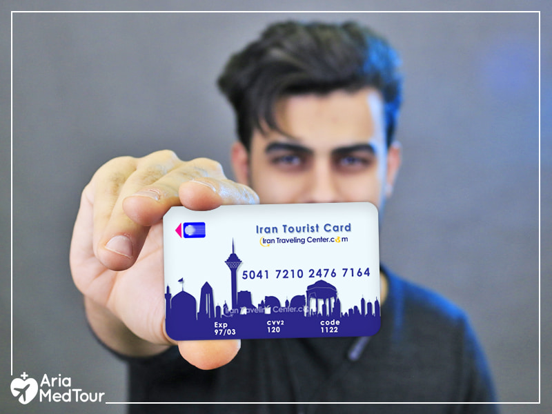 man holding an Iran Tourist Card up to the camera