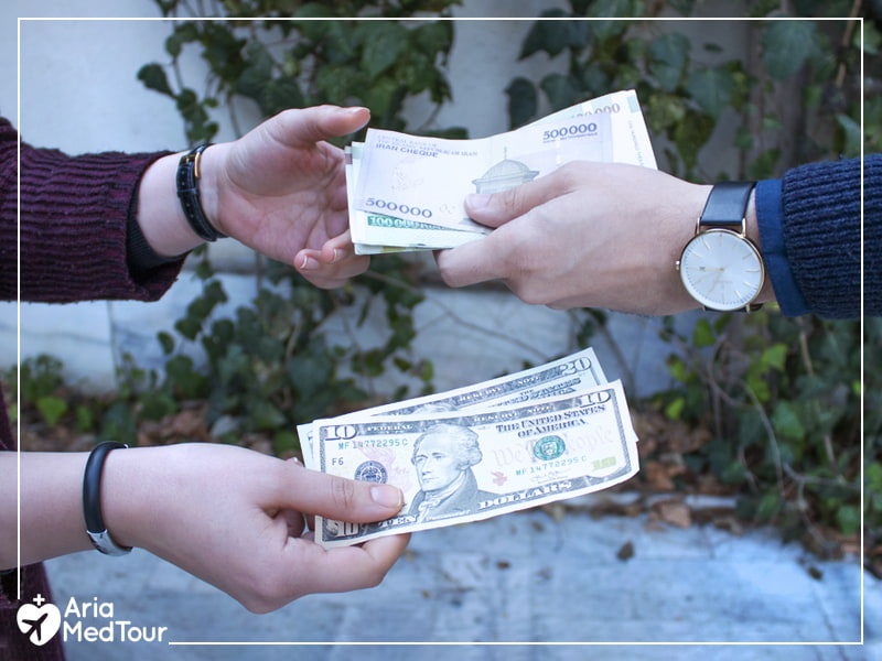 Hands exchanging dollars with Iranian money