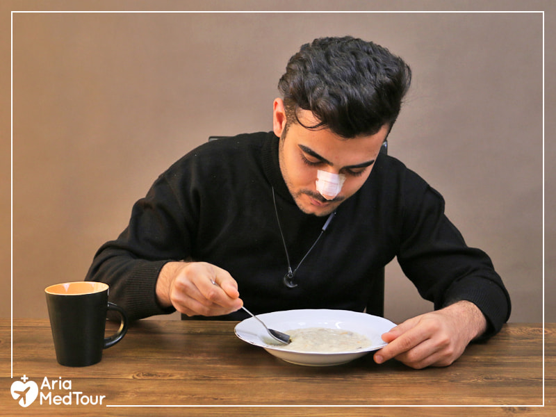 man in black eating soup after his nose job
