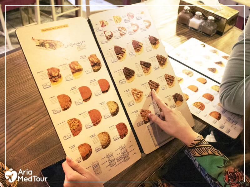 woman reading a restaurant menu in Iran