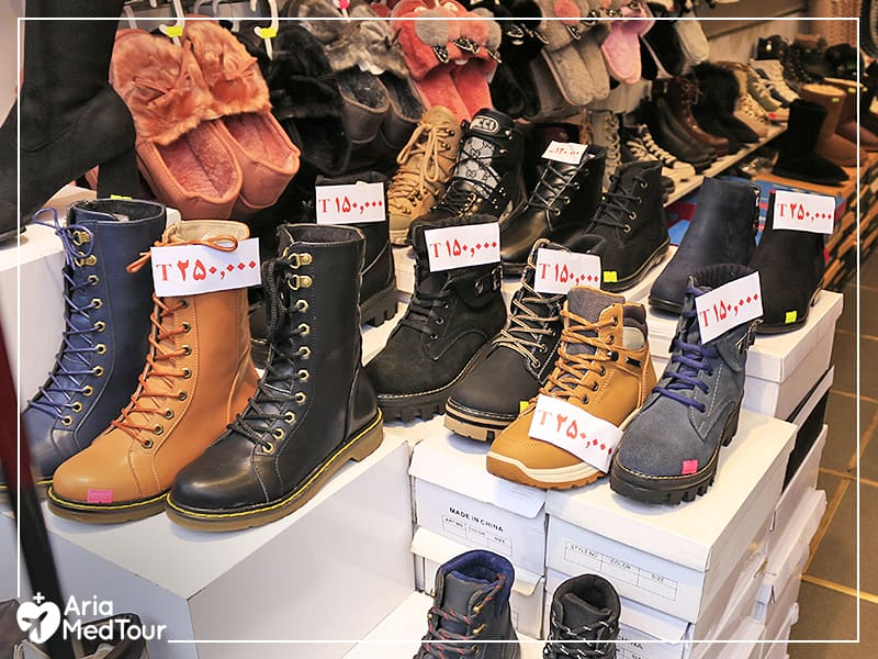 shoes and boots in the display window of an Iranian shoe shop with price tags denominated in Tomans.