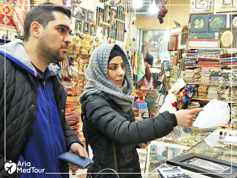 Man and woman at an Iranian traditional shop with various items seen in the background