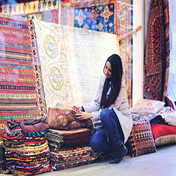 woman in carpet bazaar choosing Persian rug to buy as a souvenir