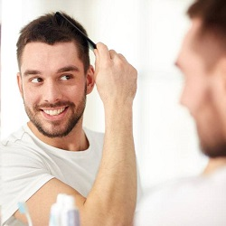 smiling man combing his hair in the mirror
