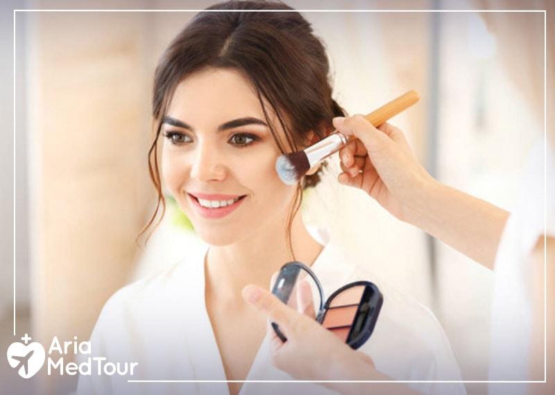 a woman applying cosmetics and putting makeup after her nose job