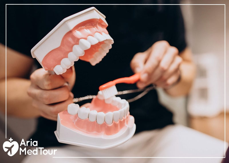 a woman cleaning dentures with a toothbrush and showing how to clean teeth after dental implants