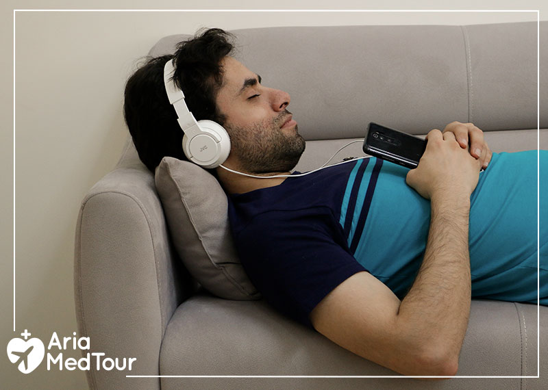 a man listening to music to relax and reduce his anxiety and stress before his surgery