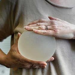 a woman with a breast implant in her hand and showing it in front of her breast
